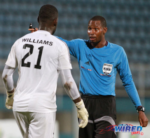 Photo: Central FC goalkeeper Jan-Michael Williams (left) queries a Rodphin Harris decision during the 2013 First Citizens Cup. (Courtesy Allan V Crane/Wired868)