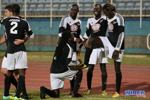 Photo: Central FC Rundell Winchester (far right) gets his boots shined by teammate Jason Marcano (stooping) after breaking his goal slump against Point Fortin Civic last night. (Courtesy Allan V Crane/Wired868)
