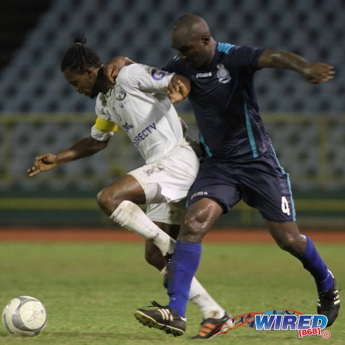 Photo: W Connection captain Gerard Williams (left) hustles the ball away from Police FC defender Karlon Murray during 2013/14 Pro League action. (Courtesy Wired868)
