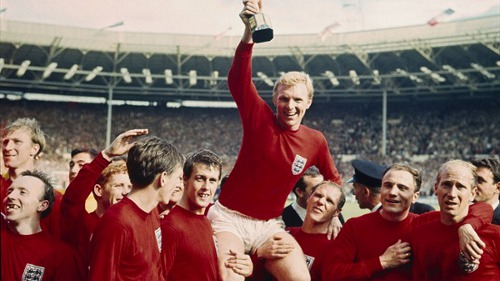 Photo: England captain Bobby Moore (centre) and his teammates celebrate with the 1966 World Cup trophy. (Courtesy the FA)