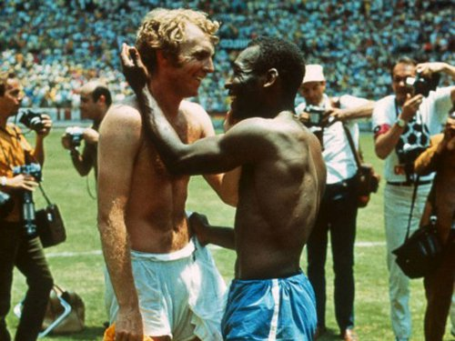 Photo: Late England World Cup captain and West Ham legend Bobby Moore (left) exchanges pleasantries with Pelé in this iconic photo. (Courtesy Independent.co.uk)