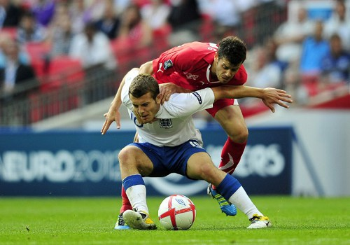 Photo: England midfielder Jack Wiltshire (foreground) screens the ball from Switzerland player Tranquillo Barnetta during a Euro 2012 qualifier. (Copyright AFP 2014/ Glyn Kirk)