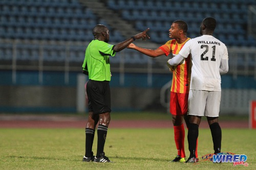 Photo: Point Fortin Civic player Andrei Pacheco (centre) shares his disgust with referee Gyasi McDonald (left) while Central FC goalkeeper Jan-Michael Williams tries to calm things down. (Courtesy Allan V Crane/Wired868)