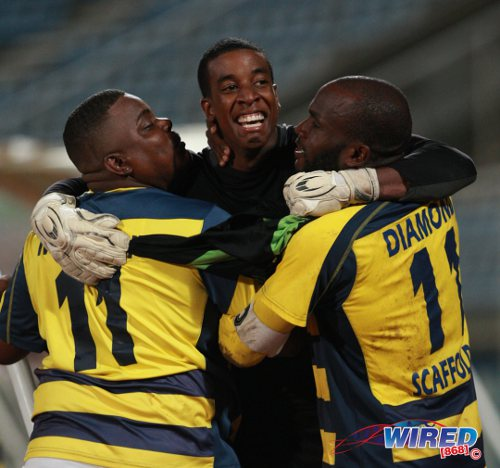 Photo: Club Sando goalkeeper Andre Marchan (centre) is congratulated by team captain Teba McKnight (right) and a supporter during the Super League team's Toyota Classic run last season. (Courtesy Allan V Crane/Wired868)