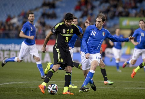 Photo: Brazil-born Spain forward Diego Costa (left) tries to get his shot past Argentina-born Italy defender Gabriel Paletta. (Copyright AFP 2014/Dani Pozo)
