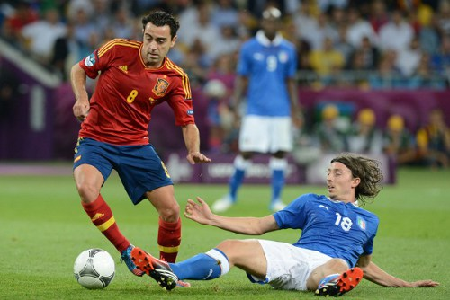 Photo: Spain playmaker Xavi (left) dances away from Italy midfielder Riccardo Montolivo. (Copyright AFP 2014/Patrick Hertzog)