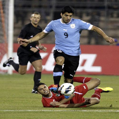 Photo: Uruguay star Luis Suarez dribbles past Jordan midfielder Saeed Al-Murjan (bottom) during their FIFA Play Off match last November. (Copyright AFP 2014: Khalil Mazraawi)