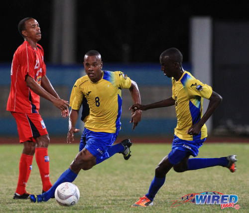 Photo Defence Force midfielder Curtis Gonzales (centre) advances alongside teammate Jerwyn Balthazar (right) while Caledonia AIA playmaker Densill Theobald looks distraught. (Courtesy Allan V Crane/Wired868)