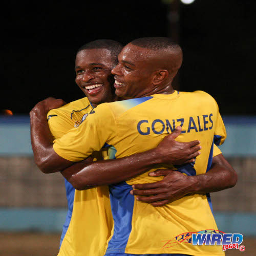 Photo: Defence Force players Josimar Belgrave (left) and Curtis Gonzales celebrate as the defending champions pulled within a point of the Pro League summit. (Courtesy Allan V Crane/Wired868)