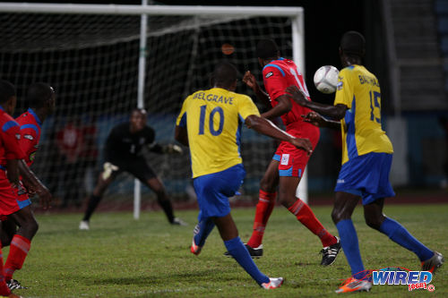 Photo: Defence Force midfielder Josimar Belgrave (centre) curls his shot around St Ann's Rangers defender Tevin Gilkes and into the far corner. (Courtesy Allan V Crane/Wired868)