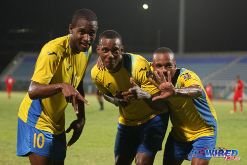 Photo: Defence Force players (from left) Josimar Belgrave, Rodell Elcock and Curtis Gonzales celebrate during their 4-0 conquest of Caledonia AIA last week. (Courtesy Allan V Crane/Wired868)