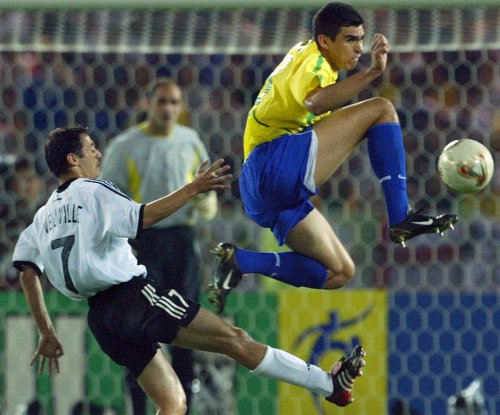 Photo: Brazil defender Lucio (right) beats Germany's forward Oliver Neuville to the ball during the 2002 World Cup final.  (Copyright AFP 2014/Patrick Hertzog)
