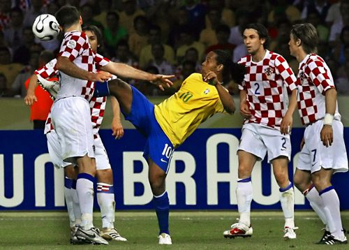 Photo: Brazil midfielder Ronaldinho (centre) controls the ball between a quartet of Croatian opponents. (Copyright AFP 2014/Antonio Scorza)