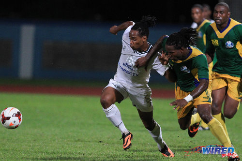 Photo: W Connection attacker Neil Benjamin Jr (left) tries to escape from Guaya right back Leroy Jones during the 2013 Toyota Classic semi-finals. Benjamin struck twice against Police FC yesterday. (Courtesy Allan V Crane/Wired868)