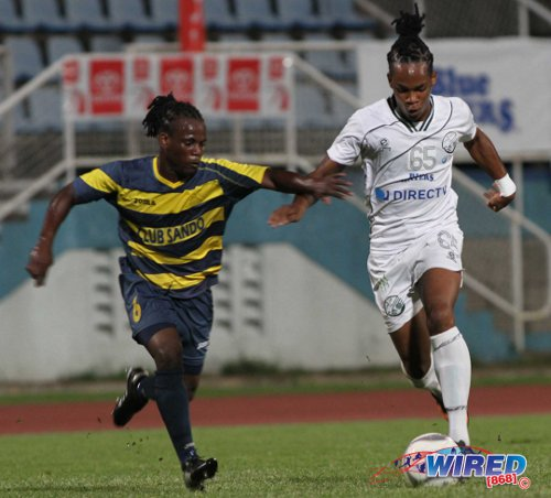 Photo: W Connection attacker Neil Benjamin Jr (right) runs at Club Sando fullback Kemuel Rivers during the 2013 Toyota Cup. (Courtesy Allan V Crane/Wired868)
