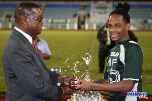 Photo: W Connection attacker Neil Benjamin Jr (right) collects his TTFA FA Trophy MVP award from TTFA president Raymond Tim Kee. (Courtesy Wired868)