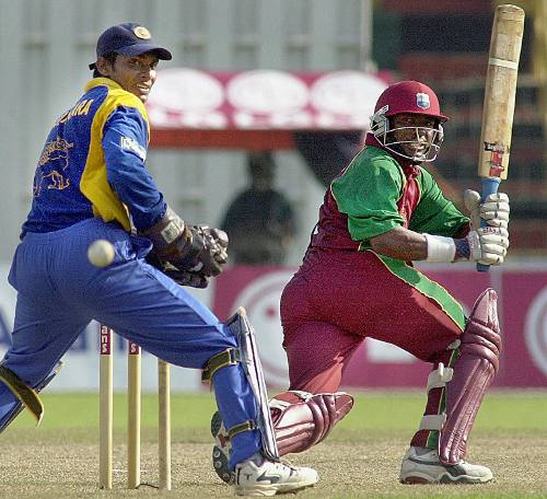 Photo: Former West Indies batsman Brian Lara sweeps to the boundary as Sri Lankan wicketkeeper Kumar Sangakkara looks on.    (Copyright AFP 2014/Sena Vidanagama)