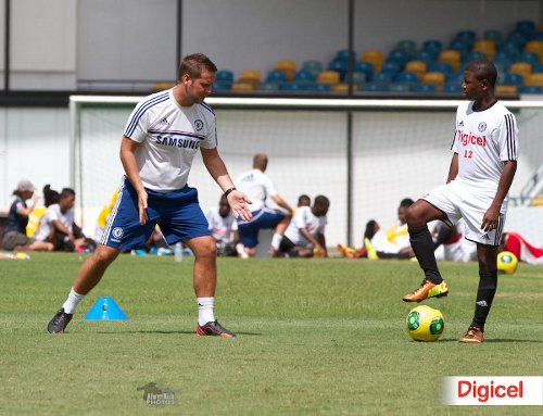 Photo: A Chelsea coach (left) offers advice to a young player during the 2013 Digicel Clinic. (Courtesy Alwyn King/Digicel)