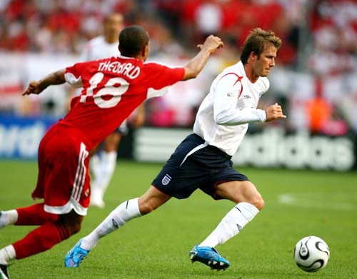Photo: Former England star David Beckham (right) tries to escape from Trinidad and Tobago midfielder Densill Theobald.