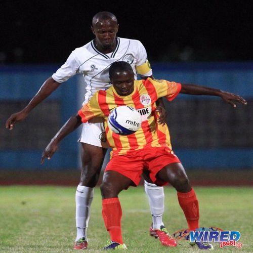 Photo: W Connection defender Daneil Cyrus (back) keeps a close watch on Point Fortin Civic attacker Sylvester Teesdale in the 2014 Lucozade Sport Goal Shield semifinal. (Courtesy Allan V Crane/Wired868)