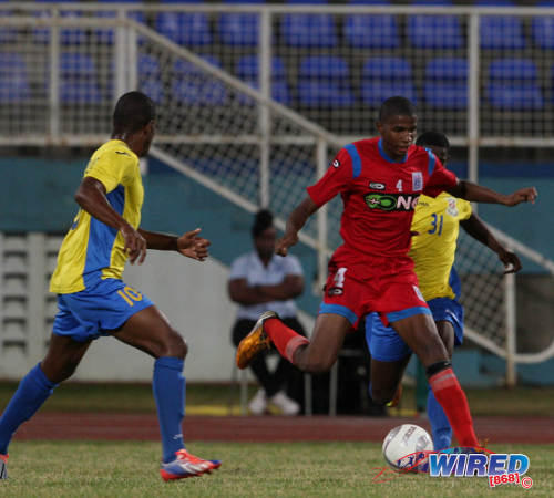 Photo: St Ann's Rangers utility player Jelani Peters (centre) looks for a teammate against Defence Force in a Pro League fixture. (Courtesy Allan V Crane/Wired868)