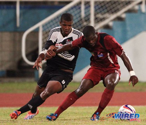 Photo: Central FC forward Dwight Quintero (left) tries to slow down North East Stars defender Glenton Wolfe. (Courtesy Allan V Crane/Wired868)