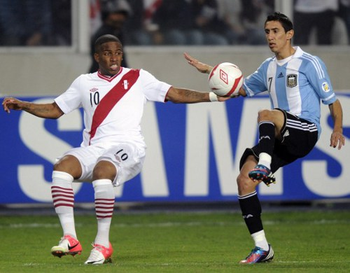 Photo: Argentina midfielder Angel Di Maria (right) prepares to flick the ball over the head of Peru player Jefferson Farfan during a 2014 World Cup qualifier.    (Copyright AFP 2014/Ernesto Benavides)
