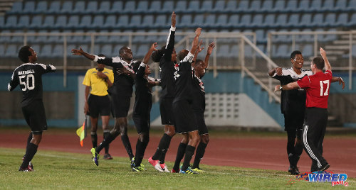 Photo: Central FC striker Willis Plaza (second from right) is congratulated by head coach Terry Fenwick while Marvin Oliver and his teammates join in during a 2013/14 Pro League fixture. (Courtesy Allan V Crane/Wired868)