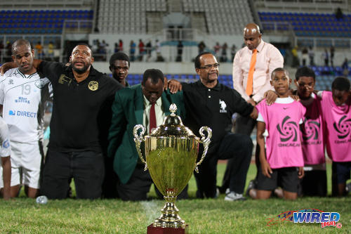 Photo: Then W Connection chairman David John-Williams (second from left), coach Stuart Charles-Fevrier (centre) and defender Joel Russell (far left) say a prayer of thanks after securing the 2013/14 Pro League trophy at the Ato Boldon Stadium in Couva. (Courtesy Allan V Crane/Wired868)