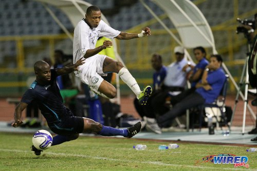 Photo: W Connection winger Stefano Rijssel (right) hurdles a tackle from Police FC defender Anton Hutchinson during the Digicel Pro Bowl final. (Courtesy Allan V Crane/Wired868)