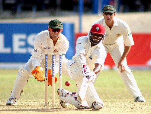 Photo: West Indies cricket star Brian Lara sweeps for four runs against Australia at the Queen's Park Oval in Port of Spain, Trinidad on 20 April, 2003.  Behind stumps are Australian wicket keeper Adam Gilchrist (left) and Mathew Hayden.   (Copyright AFP 2014/Robert Taylor)