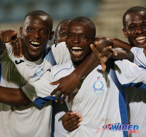Photo: Police FC brothers Jameel (left) and Kareem Perry (centre) celebrate during a Pro League knock out affair in the 2013/14 season. (Courtesy Allan V Crane/Wired868)