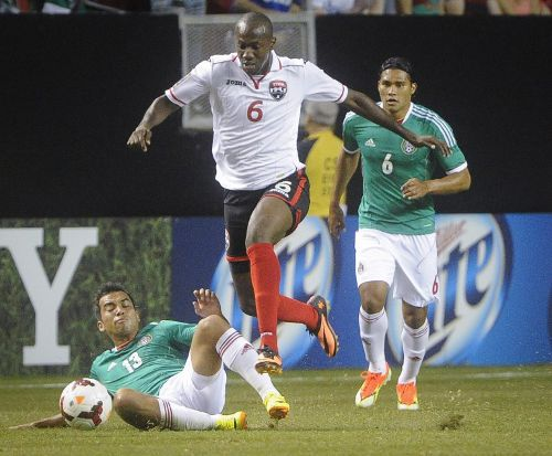 Photo: Trinidad and Tobago's Daniel Cyrus (centre) hudles Mexico player Adrian Aldrete (left) while his teammate Carlos Pena looks on in the 2013 Gold Cup quarterfinal at the Georgia Dome in Atlanta.     (Copyright AFP 2014/ John Amis)