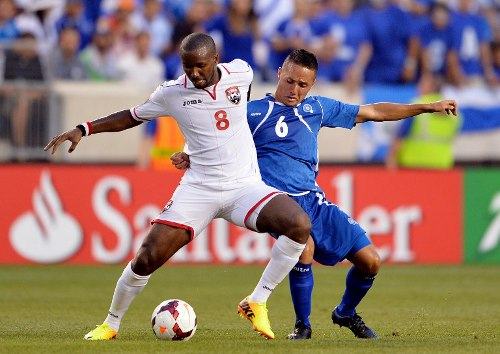 Photo: Trinidad and Tobago midfielder Khaleem Hyland (left) holds off El Salvador player Richard Menjivar during the 2013 CONCACAF Gold Cup.  (Copyright AFP 2014/Stan Honda)