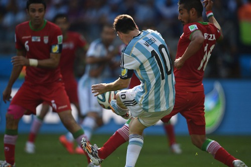 Photo: Argentina forward and captain Lionel Messi (centre) curls the ball around his warden for the winner against Iran.    (Copyright AFP 2014/Pedro Ugarte)