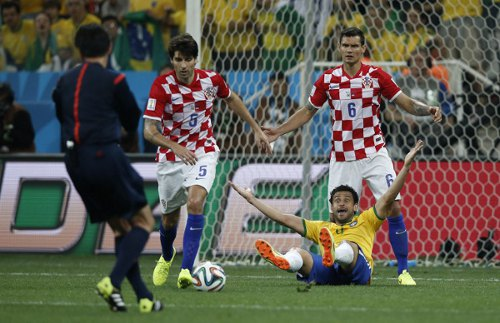 Photo: Brazil forward Fred (front) asks referee Yuichi Nishimura for a cushion. Nishimura mistakenly gave him a penalty instead. (Copyright AFP 2014/Adrian Dennis)