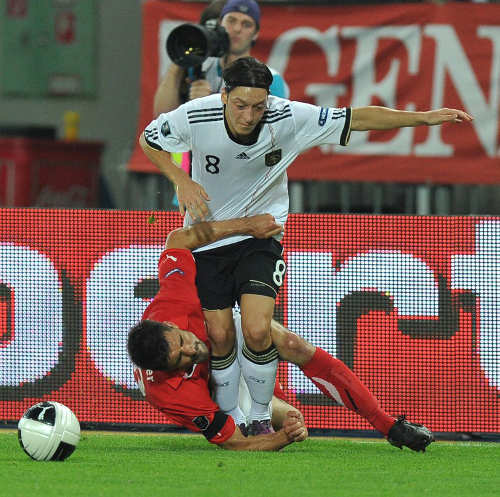 Photo: Germany playmaker Mesut Özil (standing) tries to escape a desperate challenge from Austria midfielder Paul Scharner during a Euro 2012 qualifier. (Copyright AFP 2014/Joe Klamar)
