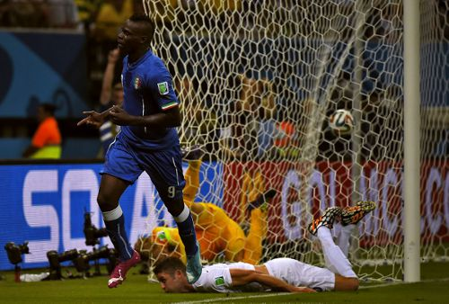 Photo: Italy forward Mario Balotelli (front) celebrates his country's winning goal against England at the Amazonia Arena in Manaus today.   (Copyright AFP 2014/Fabrice Coffrini)