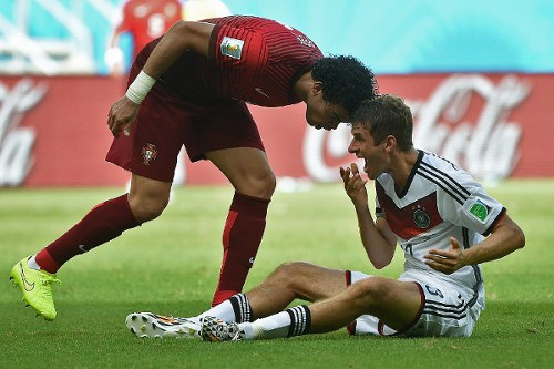 Photo: Portugal defender Pepe (right) leans in on Germany forward Thomas Müller before being sent off during the Group G contest. (Copyright AFP 2014/Patrik Stollarz)