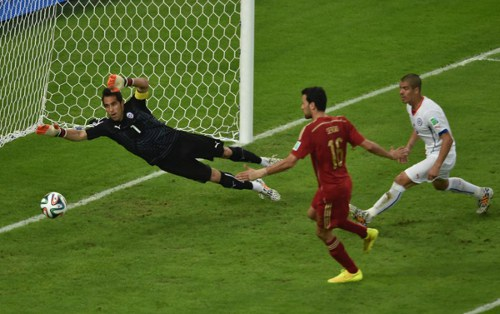 Photo: Spain midfielder Sergio Busquets (centre) misses a clear scoring chance while Chile goalkeeper and captain Claudio Bravo looks on. (Copyright AFP 2014/Yasuyoshi Chiba)