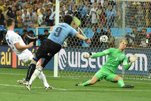 Photo: Uruguay forward Luis Suarez (centre) blasts the ball past England goalkeeper Joe Hart (right) while defender Tim Cahill watches on during the Brazil 2014 World Cup. (Copyright AFP 2014/Luis Acosta)