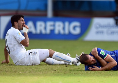 Photo: Uruguay forward Luis Suarez (left) discovers that Italy defender Giorgio Chiellini surprisingly tastes nothing like panini. (Copyright AFP 2014/Javier Soriano)