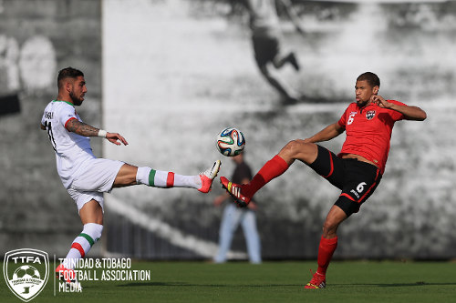 Photo: Trinidad and Tobago defender Radanfah Abu Bakr (right) challenges Iran forward Ashkan Dejagah for the ball during a friendly in June 2014. Abu Bakr is also the son of Jamaat-al-Muslimeen Imam Yasin Abu Bakr. (Courtesy Allan V Crane/TTFA Media)