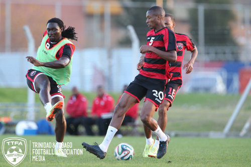 Photo: Trinidad and Tobago captain Kenwyne Jones (left) drives a shot past teammate Kevan George (centre) during a training session in Buenos Aires. (Courtesy Allan V Crane/TTFA Media)