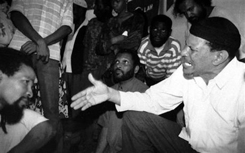 Photo: Yasin Abu Bakr (right) speaks to fellow Jamaat-al-Muslimeen members shortly after their release from prison in 1992. (Copyright AP)