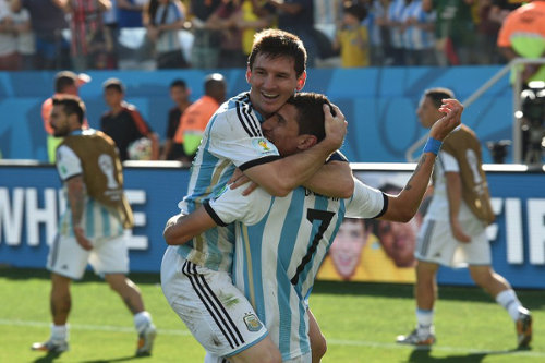 Photo: Argentina captain Lionel Messi (left) celebrates with goal scorer Angel Di Maria after the latter's decisive goal against Switzerland.      (Copyright AFP 2014/Nelson Almeida)