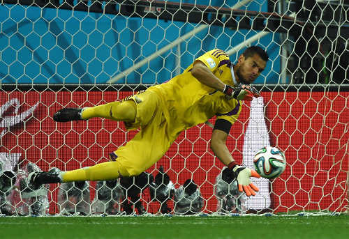 Photo: Argentina goalkeeper Sergio Romero keeps out a penalty from Netherlands defender Ron Vlaar in the 2014 World Cup semifinals. (Copyright AFP 2014/Pedro Ugarte)
