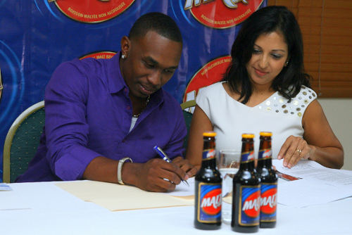 Photo: West Indies ODI captain Dwayne Bravo (left) signs on as the brand ambassador for Malta Carib while marketing manager Cindy Lutchman looks on. (Copyright David Wears)