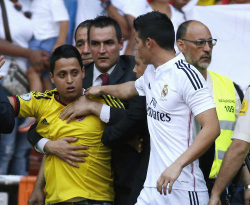 Photo: New Real Madrid signing James Rodriguez (right) intervenes for a fan during his unveiling.