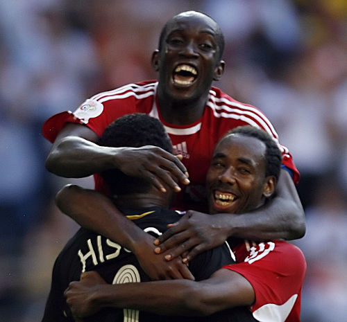 Photo: Trinidad and Tobago World Cup players Dwight Yorke (top), Dennis Lawrence (right) and Shaka Hislop celebrate after an opening goalless draw against Sweden in Dortmund, Germany. (Copyright AFP 2014/Aris Messinis)